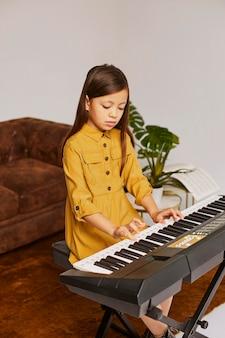 집에서 전자 키보드를 재생하는 방법을 배우는 어린 소녀