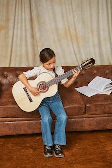 집에서 기타를 연주하는 방법을 배우는 어린 소녀
