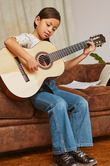 Молодая девушка учится играть на гитаре дома