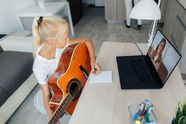 기타 연주 방법을 배우는 어린 소녀
