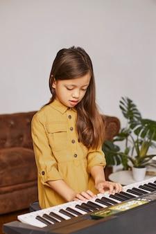 Молодая девушка учится играть на электронной клавиатуре