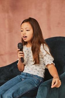 家で歌う方法を学ぶ少女