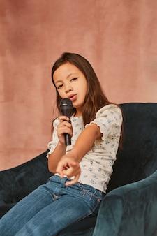 Молодая девушка учится петь дома