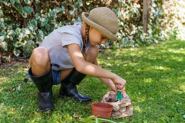 뒷마당에서 새로운 냄비에 식물을 이식하는 과정을 배우는 어린 소녀
