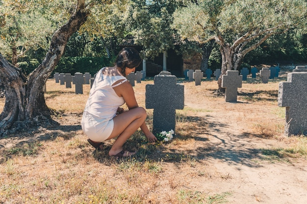 Young girl leaving flowers on a grave