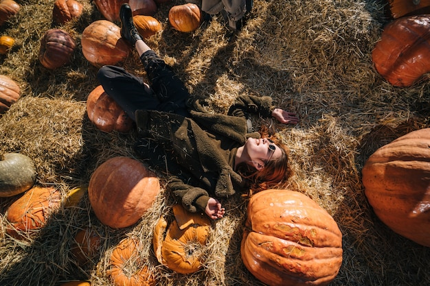 Young girl lie on haystacks among pumpkins. view from above