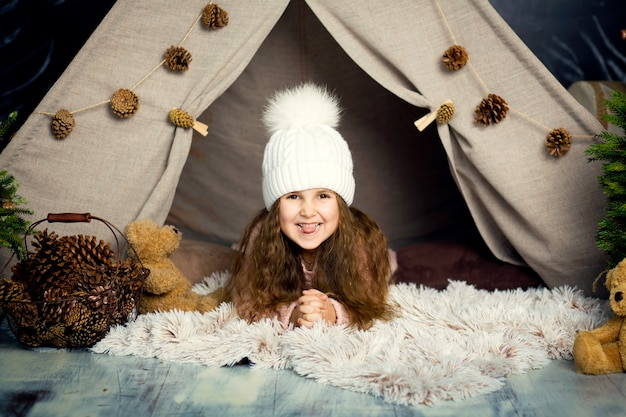 Young girl lie on pillow in christmas decorations