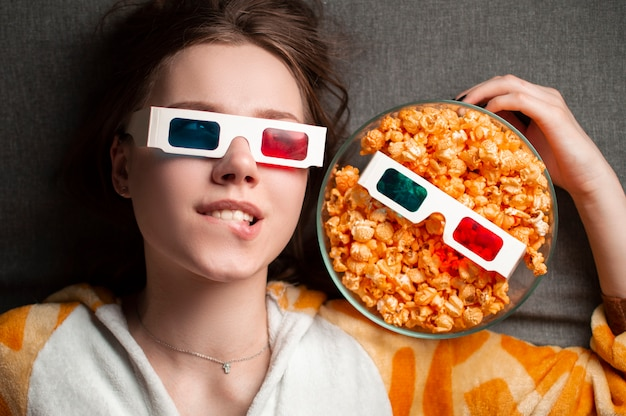 Young girl lies on a gray background in 3d glasses eats popcorn and watches a movie