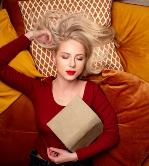 Young girl lies on a pillow with a book Premium Photo