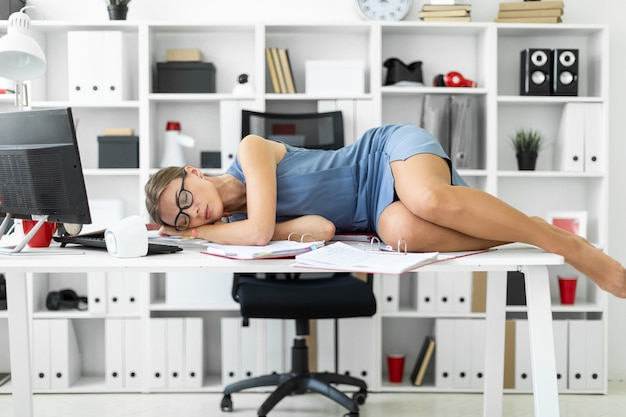Young girl lies with closed eyes on documents on desk in office.