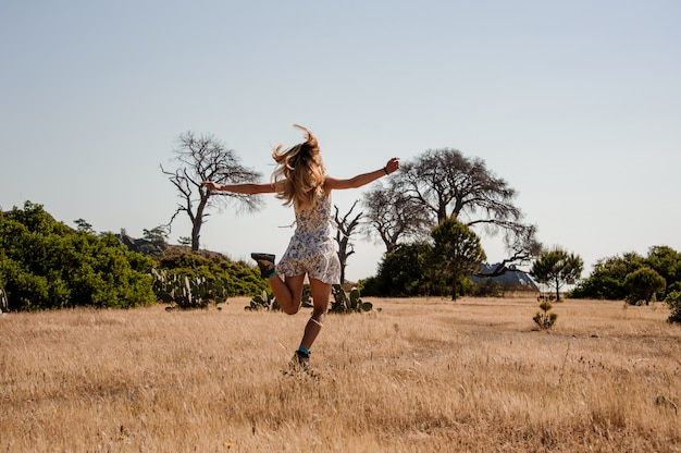 Young girl in light dress jumps on a field