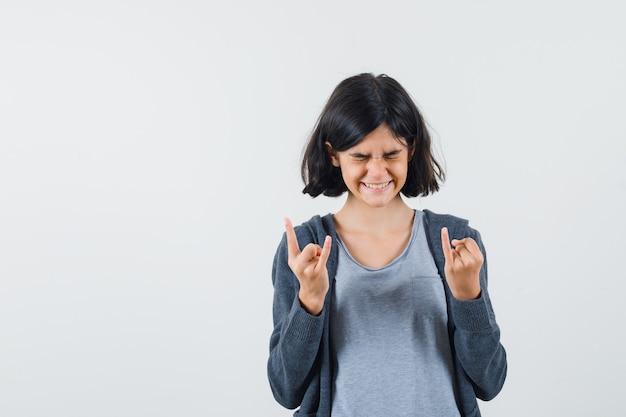 Giovane ragazza in t-shirt grigio chiaro e felpa con cappuccio con zip grigio scuro che mostra le corna delle mani mentre fa smorfie e sembra divertita