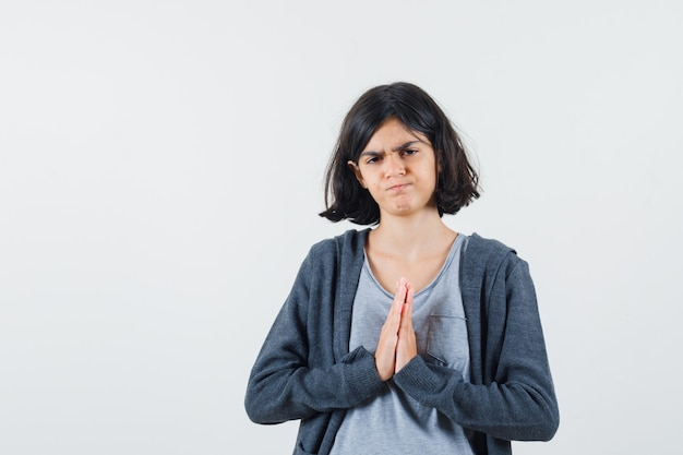 Young girl in light gray t-shirt and dark grey zip-front hoodie showing namaste gesture and looking serious