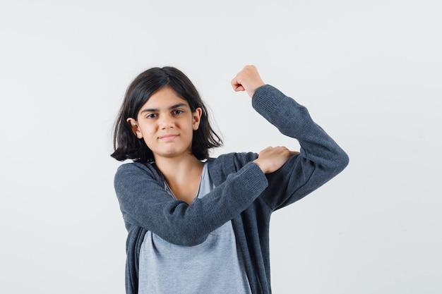 Giovane ragazza in t-shirt grigio chiaro e felpa con cappuccio con zip grigio scuro che mostra il gesto di potenza e sembra carina,