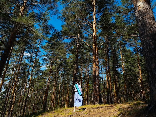 A young girl in a light skirt walks through the forest and carries yoga mats behind her back