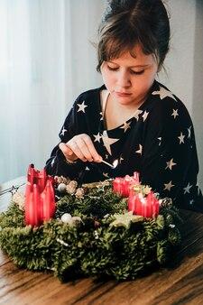 スイスのクリスマスの1週間前にアドベントリースの最後の4番目のキャンドルを灯している少女