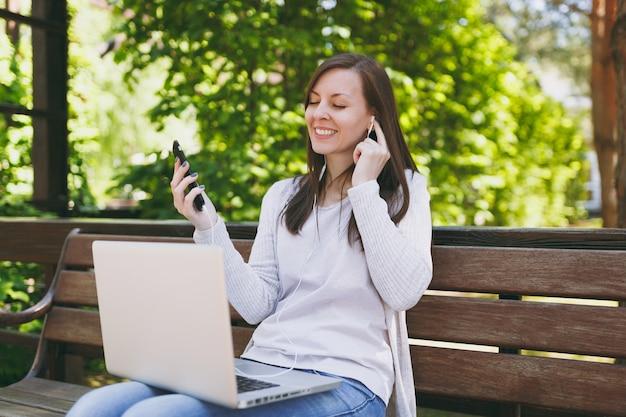 Молодая девушка слушает музыку в мобильном телефоне с наушниками. женщина сидит на скамейке, работая на современном портативном компьютере в городском парке на улице на открытом воздухе на природе. мобильный офис. бизнес-концепция фрилансера