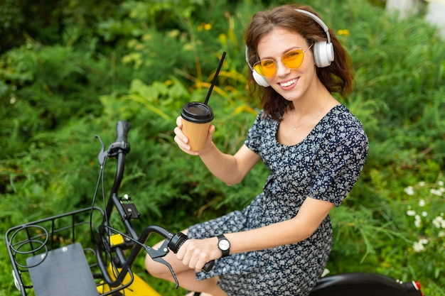 Young girl listen to music and ride a bike in the park with cup of coffee
