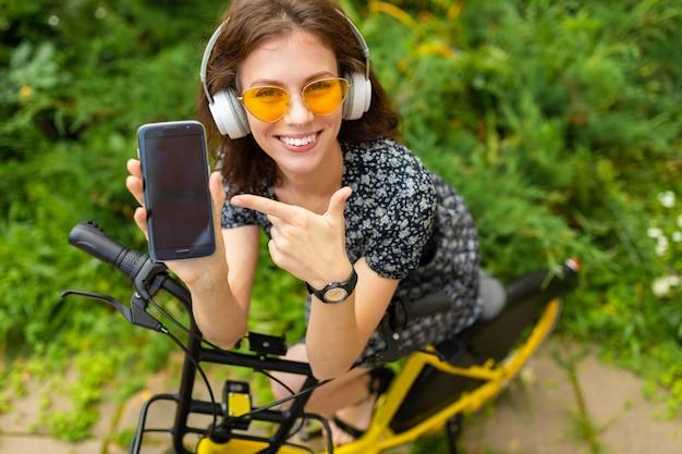 若い女の子は音楽を聴くと素晴らしい気分で公園で自転車に乗る