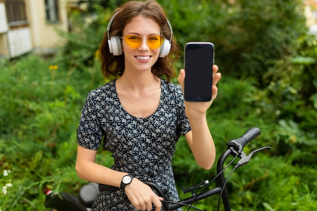 若い女の子は音楽を聴くし、彼女の電話で公園で自転車に乗る