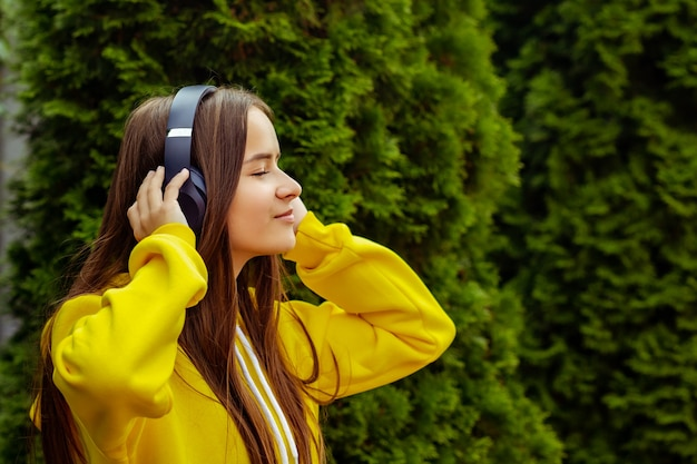 Young girl listening to mp3 player on the street with headphones, smiling