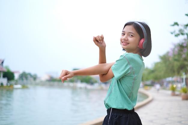 音楽を聴くと公園でスポーツをしている若い女の子。