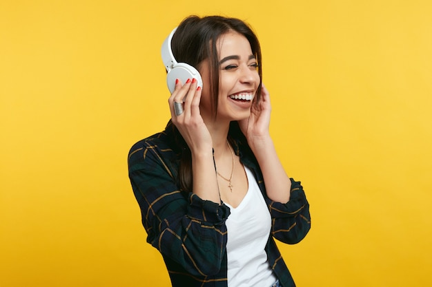 Молодая девушка слушает музыку и улыбается над желтой студией