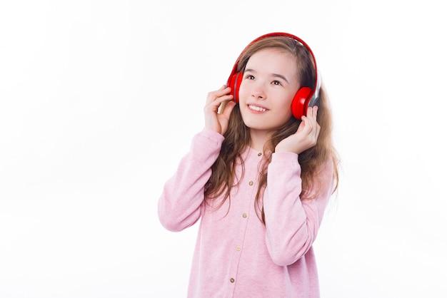 白い壁の上のヘッドフォンで音楽を聞いている少女