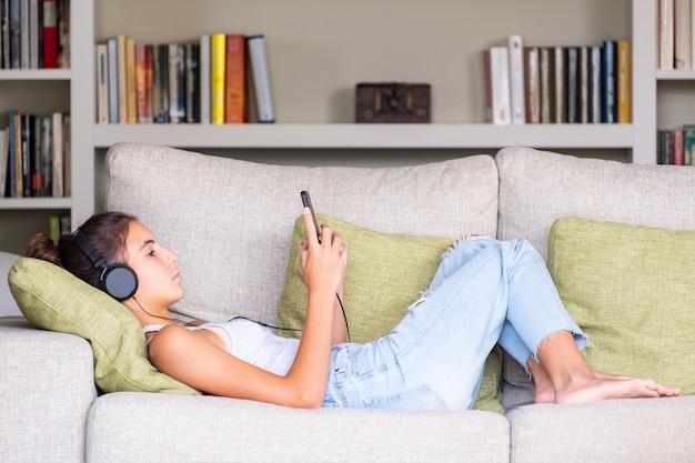 Молодая девушка прослушивания музыки в наушниках на диване у себя дома