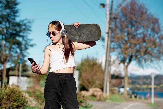 Молодая девушка слушает музыку со своего мобильного телефона со скейтбордом на плечах голубое небо и деревья на заднем плане