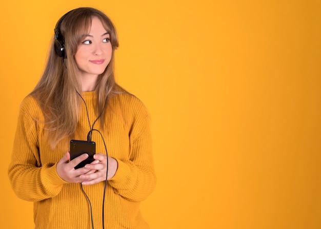 黄色の背景にヘッドフォンで幸せな彼女のスマートフォンで音楽を聴く若い女の子
