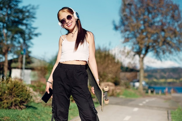 スケートボードを手に音楽を聴いて笑っている少女。青い空と背景の木々