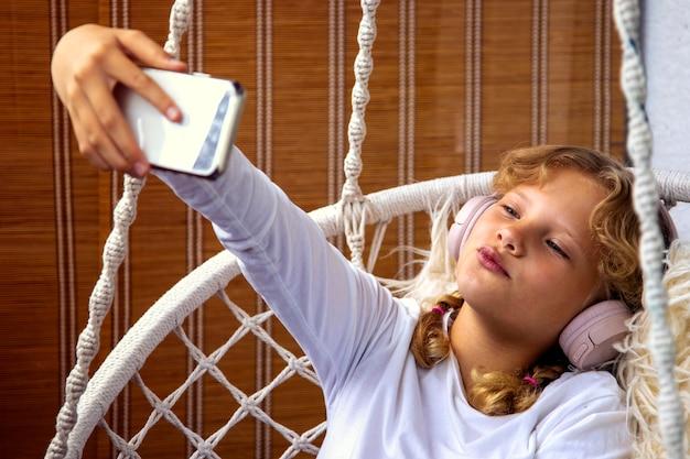Молодая девушка слушает музыку в наушниках на своем мобильном телефоне и делает селфи