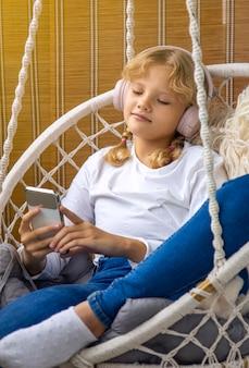 Молодая девушка слушает музыку в наушниках на своем мобильном телефоне, сидя в гамаке на балконе
