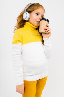 Young girl listens to music in big headphones and drinks coffee