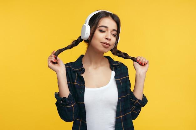 Молодая девушка слушает музыку в белых наушниках с закрытыми глазами