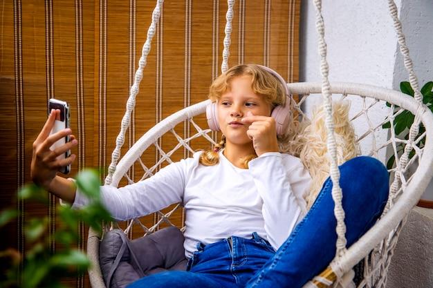 Молодая девушка слушает музыку в наушниках на своем мобильном телефоне и делает селфи, сидя в гамаке на балконе