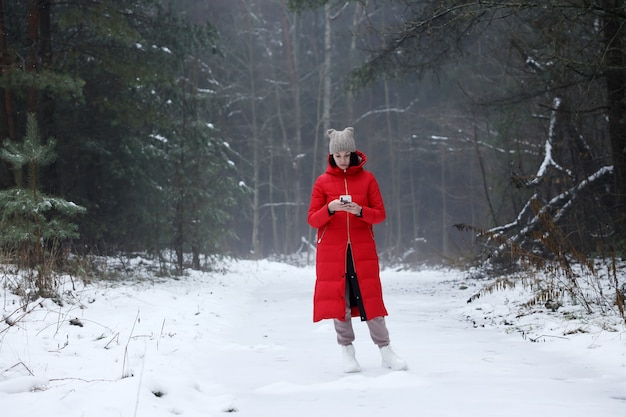 A young girl in a long red down-padded coat stands in the winter forest.