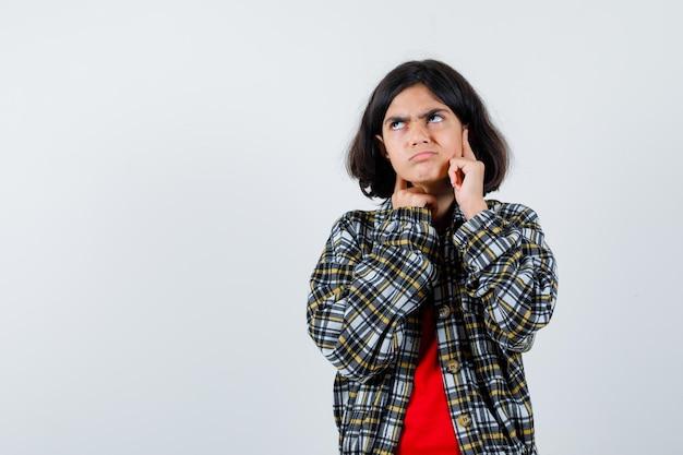 チェックのシャツと赤いtシャツの顔に人差し指を置き、物思いにふけるように見ている若い女の子。正面図。