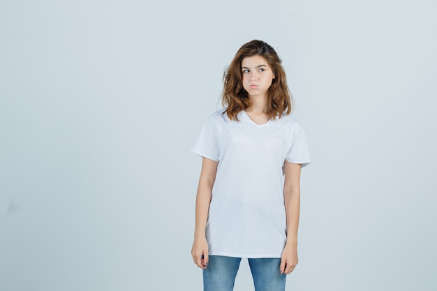 Young girl looking aside, blowing cheeks in white t-shirt and looking disappointed. front view. Free Photo