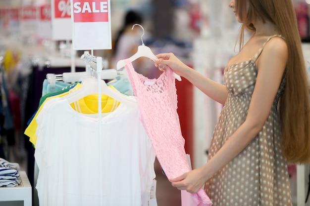 若い女の子はピンクのドレスを見て Premium写真