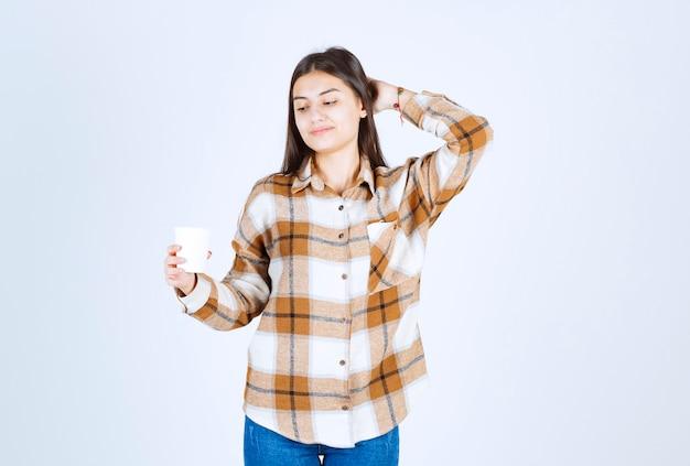 흰 벽에 있는 차 한 잔을 보고 있는 어린 소녀.