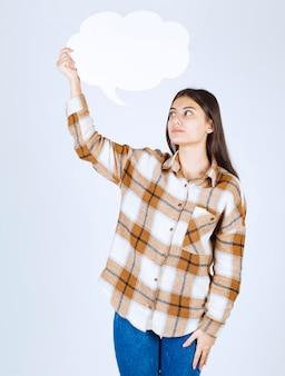 白い壁に空のテキストの雲を見ている若い女の子。