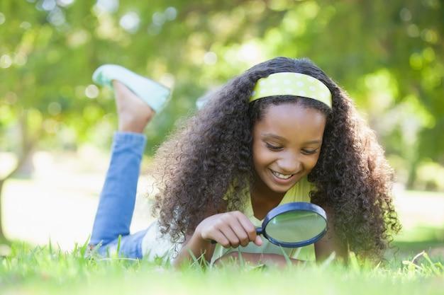 어린 소녀는 공원에서 돋보기를 통해 잔디를보고