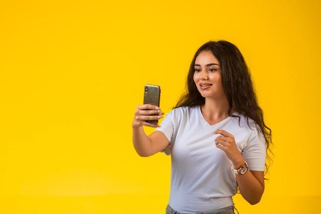 Молодая девушка смотрит на свой телефон и делает селфи.