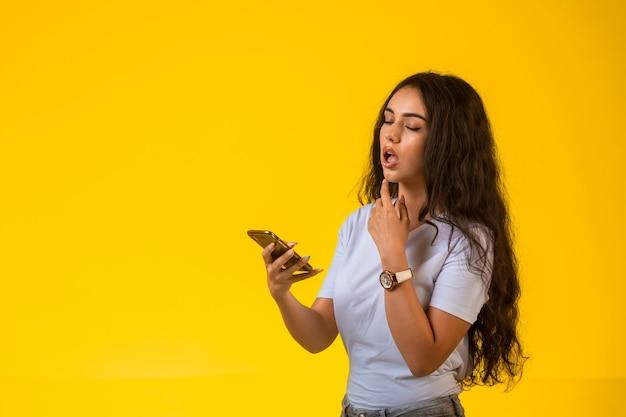 Молодая девушка смотрит на свой телефон и думает