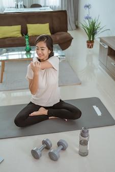 ノートパソコンを見て、自宅で自分で運動をしている少女