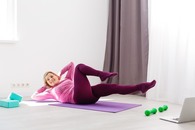 ノートパソコンを見て、自宅で運動をしている少女。