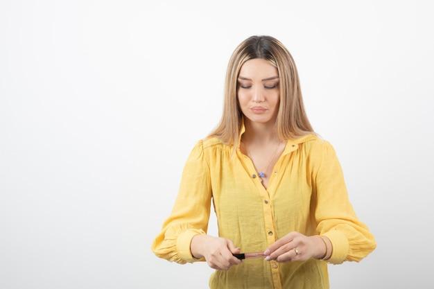 Молодая девушка, глядя на помаду в руках.