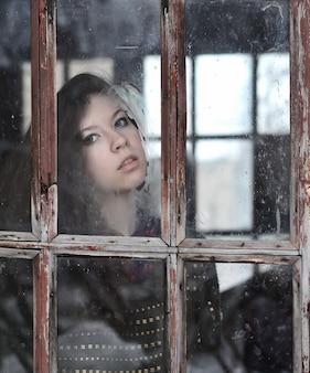 古い窓からすを通してカメラを見て若い女の子